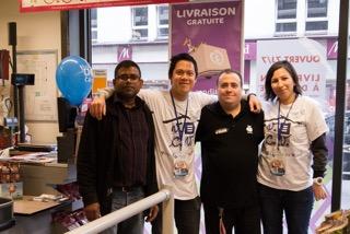 Deux bénévoles avec le sous-directeur et un agent de caisse du magasin